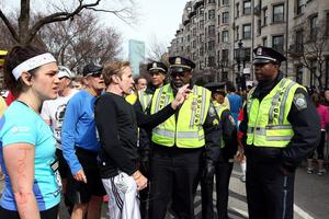 BOSTON, MA - APRIL 15:  Runners talk to Boston Police near Kenmore Square after two bombs exploded during the 117th Boston Marathon on April 15, 2013 in Boston, Massachusetts. Two people are confirmed dead and at least 28 injured after at least two explosions went off near the finish line to the marathon.  (Photo by Alex Trautwig/Getty Images)