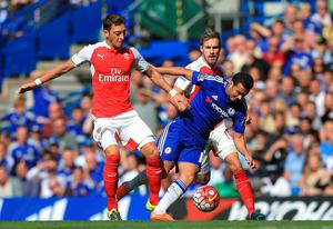 """Chelsea's Pedro (right) in action with Arsenal's Mesut Ozil (left) and Aaron Ramsey during the Barclays Premier League match at Stamford Bridge, London. PRESS ASSOCIATION Photo. Picture date: Saturday September 19, 2015. See PA story SOCCER Chelsea. Photo credit should read: John Walton/PA Wire. RESTRICTIONS: EDITORIAL USE ONLY No use with unauthorised audio, video, data, fixture lists, club/league logos or """"live"""" services. Online in-match use limited to 45 images, no video emulation. No use in betting, games or single club/league/player publications."""
