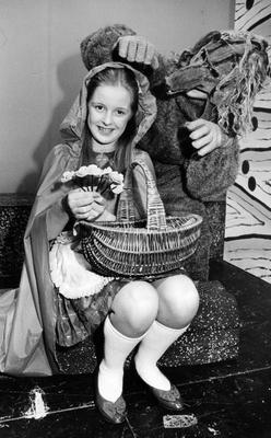Little Red Ridding Hood, played by Tara Mills, makes a posy with some flowers in the woods as Wolf, Trevor Furness, comes up behind her in a scene from the Belvoir Players Pantomine 'Red Riding Hood' at the Group Theatre, Belfast.  29/12/1983