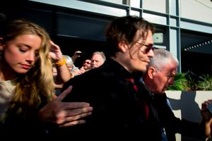 """US moviestar Johnny Depp (C) and his wife Amber Heard (L) leave the Gold Coast Courthouse in the Gold Coast on April 18, 2016.   Depp's wife Amber Heard pleaded guilty on April 18 to falsifying immigration documents in a case dubbed the """"war on terrier"""" after she brought her two pet dogs on their private jet into Australia last year. / AFP PHOTO / Patrick HAMILTONPATRICK HAMILTON/AFP/Getty Images"""
