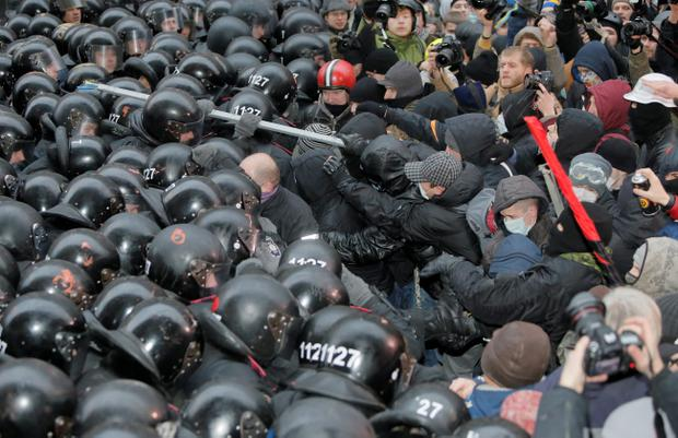 Protesters clash with police at the presidential office in Kiev, Ukraine, on Sunday, Dec. 1, 2013. As many as 100,000 demonstrators chased away police to rally in the center of Ukraine's capital on Sunday, defying a government ban on protests on Independence Square, in the biggest show of anger over the president's refusal to sign an agreement with the European Union. (AP Photo/Efrem Lukatsky)