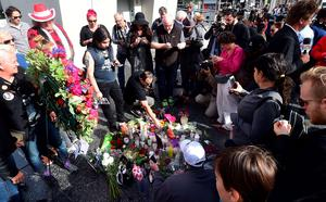 """People pay their respects at the Hollywood Star of the late British musician David Bowie in Hollywood, California, on January 11, 2016. Bowie died at the age of 69 after a secret battle with cancer, prompting a cascade of tributes for one of the most influential and innovative artists of his time. A notoriously private person, Bowie's death was a shock with his death coming just two days after he released his 25th studio album """"Blackstar"""", on his 69th birthday on January 8. """"David Bowie died peacefully today (Sunday) surrounded by his family after a courageous 18-month battle with cancer,"""" said a statement posted January 11on his official social media accounts.  AFP PHOTO/FREDERIC J. BROWNFREDERIC J. BROWN/AFP/Getty Images"""