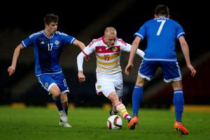 Scotland's striker Steven Naismith (C) runs with the ball pressured by Northern Ireland's defender Paddy McNair (L) during the international friendly football match between Scotland and Northern Ireland at Hampden Park in Glasgow, Scotland on March 25, 2015. Scotland won 1-0.  AFP PHOTO / IAN MACNICOLIan MacNicol/AFP/Getty Images
