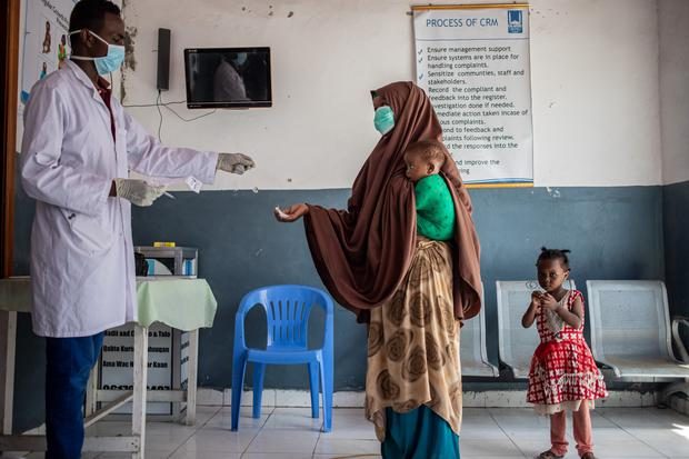A mother and her children wait in a health clinic in the Bondhere district of Mogadishu in May 2020. The infrastructure in Somalia is struggling to cope with COVID-19. Photo: Arete/ Ismail Taxta/ DEC