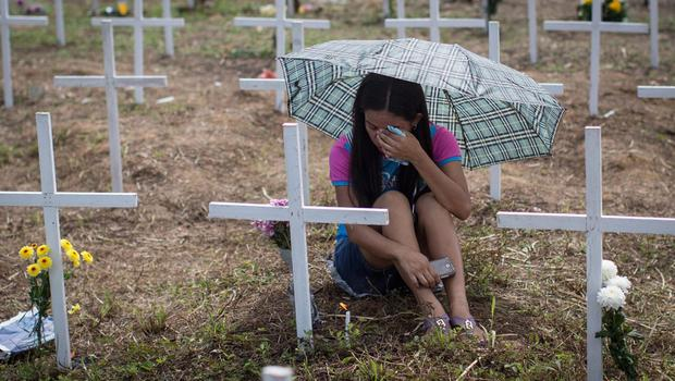 A woman cries at the cross of a loved one at the mass grave on the grounds of the Holy Cross Memorial Garden on November 8, 2014 in Tacloban, Leyte, Philippines. Residents and typhoon survivors from across the central Philippines attended memorial services and visited mass graves honouring those who lost their lives one year ago when Typhoon Haiyan, the strongest typhoon ever to make landfall, swept across the region, leaving more than 6000 dead and many more homeless.  (Photo by Chris McGrath/Getty Images)