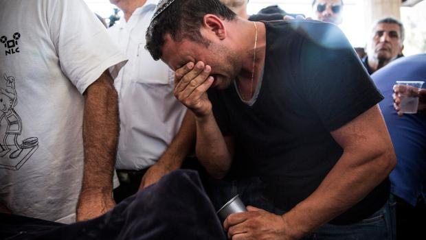 "YAHUD MONOSON, ISRAEL - JULY 16:  People mourn during the funeral of Dror Khenin at a cemetary on July 16, 2014 in Yahud Monoson, Israel. Yesterday Khenin was the first Israeli to be killed by a Hamas motar as he offered food to Israeli soldiers working near the Erez border crossing between Israel and Gaza. As Operation ""Decisive Edge"" enters its ninth day, over 200 Palestinians have been killed in Israeli missile strikes.  (Photo by Andrew Burton/Getty Images)"