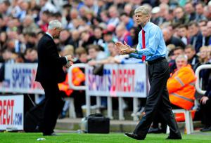 NEWCASTLE UPON TYNE, ENGLAND - MAY 19:  Managers Arsene Wenger (R) of Arsenal encourages his players as Alan Pardew of Newcastle walks back to his seat during the Barclays Premier League match between Newcastle United and Arsenal at St James' Park on May 19, 2013 in Newcastle upon Tyne, England.  (Photo by Stu Forster/Getty Images)