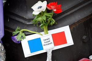 "Flowers and a note in the French national colors, reading France's motto ""Liberty, Equality, Fraternity"" is pictured near the cordoned off crime scene of the Bataclan concert hall on November 16, 2015 in Paris, three days after the terrorist attacks that left over 130 dead and more than 350 injured. France prepared to fall silent at noon on November 16 to mourn victims of the Paris attacks after its warplanes pounded the Syrian stronghold of Islamic State, the jihadist group that has claimed responsibility for the slaughter. AFP PHOTO / BERTRAND GUAYBERTRAND GUAY/AFP/Getty Images"