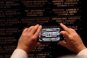 NEW YORK, NY - SEPTEMBER 08:  Family mambers photograph the names of loved ones at a ceremony at the Fire Department of New York headquarters where names were added to a memorial wall for deaths related to World Trade Center illnesses on September 8, 2015 in New York City. A total of 21 names were added to the memorial which was unveiled in September 2011 and already lists the names of 89 FDNY members who died of illnesses related to their work at the World Trade Center site during and after the 9/11 attacks.  (Photo by Spencer Platt/Getty Images)