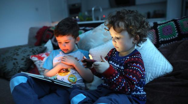 Odin (5) and Conan Bell (3) on their digital devices. Pic by Peter Morrison