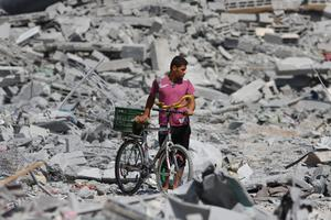 A Palestinians inspects the damage amidst rubble from destroyed houses in the heavily bombed town of Beit Hanoun, Gaza Strip, close to the Israeli border, Friday, Aug. 1, 2014.  (AP Photo/Lefteris Pitarakis)