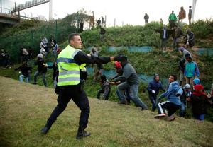 Migrants rush at a police cordon by the perimeter fence of the Eurotunnel site at Coquelles in Calais, France. PRESS ASSOCIATION Photo. Picture date: Thursday July 30, 2015. Nine people have been killed attempting to cross the Channel in the last month, according to Eurotunnel, as migrants try to reach Britain. See PA story POLITICS Calais. Photo credit should read: Yui Mok/PA Wire