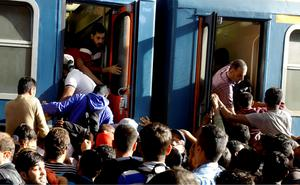 TOPSHOTS Migrants board into a local train heading to the Hungarian-Austrian border at the main train station in Budapest on September 3, 2015, after authorities re-opened the station to refugees. On the day before Hungarian authorities stopped migrants taking trains to Austria and Germany.  AFP PHOTO / PETER KOHALMIPETER KOHALMI/AFP/Getty Images