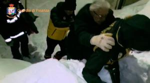 """This image grab made from a video handout released by the Guardia di Finanza on January 19, 2017 shows a man being escorted by Alpine policemen (R) and a fireman (L) outside the Hotel Rigopiano, near the village of Farinfola, on the eastern lower slopes of the Gran Sasso mountain.  """"AFP PHOTO / GUARDIA DI FINANZA HANDOUT"""" -/AFP/Getty Images"""
