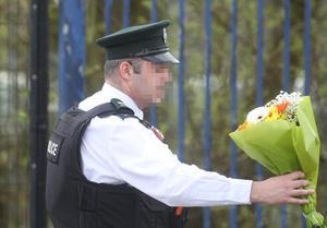 Press Eye - Belfast - Northern Ireland - 19th April 2019 -  Photo by Lorcan Doherty  / Press Eye.  The community vigil held on Fanad Drive, Creggan, following the murder of 29 years-old Lyra McKee.    PSNI officers place floral tributes left at the scene.