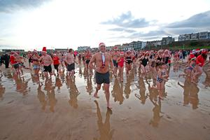 People at a charity Christmas swim at Portrush East Strand beach in Co Antrim. PRESS ASSOCIATION Photo. Picture date: Sunday December 18, 2016. Photo credit should read: Steven McAuley/PA Wire