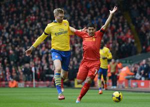 LIVERPOOL, ENGLAND - FEBRUARY 08:  Per Mertesacker of Arsenal competes with Luis Suarez of Liverpool during the Barclays Premier League match between Liverpool and Arsenal at Anfield on February 8, 2014 in Liverpool, England.  (Photo by Michael Regan/Getty Images)