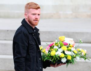 A mourner arrives carrying a wreath for the funeral service of murdered journalist Lyra McKee at St Anne's Cathedral in Belfast.