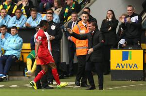 Liverpool's Raheem Sterling celebrates scoring the opening goal of the game with his manager Brendan Rodgers during the Barclays Premier League match at Carrow Road, Norwich.