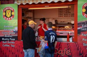 MANCHESTER, ENGLAND - APRIL 01:  Football fans buy food from a street vendor ahead of the UEFA Champions League Quarter Final first leg match between Manchester United and FC Bayern Muenchen at Old Trafford on April 1, 2014 in Manchester, England.  (Photo by Michael Regan/Bongarts/Getty Images)