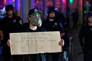 A protester wearing a gas mask stands in front of a police skirmish line during an anti-Trump protest in Oakland, California on November, 9, 2016.  Thousands of protesters rallied across the United States expressing shock and anger over Donald Trump's election, vowing to oppose divisive views they say helped the Republican billionaire win the presidency. / AFP PHOTO / Josh EdelsonJOSH EDELSON/AFP/Getty Images
