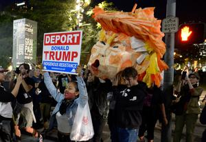 Protesters carry a paper head of President-elect Donald Trump during a protest in front of City Hall Wednesday, Nov. 9, 2016 in Los Angeles. A day after  Trumps election as president, the divisions he exposed only showed signs of widening as many thousands of protesters flooded streets across the country to condemn him.  (Keith Birmingham/The Pasadena Star-News/SCNG via AP)