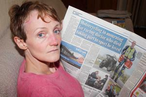 Violet McAfee reads about the death of Dr John Hinds in yesterday's Belfast Telegraph. Dr Hinds treated Violet at the North West 200 after she was hit by a bike