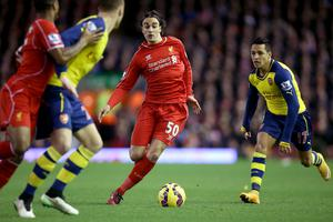 Liverpool's Lazar Markovic (centre) and Arsenal's Alexis Sanchez (right) battle for the ball during the Barclays Premier League match at Anfield, Liverpool. Peter Byrne/PA Wire.
