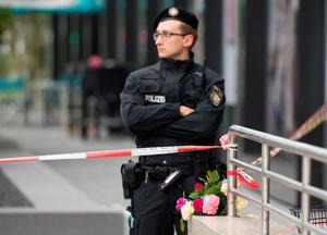 Flowers were laid near a mall where a shooting took place leaving nine people dead the day before on Saturday, July 23, 2016 in Munich, Germany. (AP Photo/Sebastian Widmann)