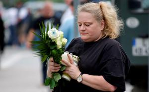 MUNICH, GERMANY - JULY 23:  A mourning woman waits with flowers and candles outside the OEZ shopping center, the day after a shooting spree left nine victims dead on July 23, 2016 in Munich, Germany. According to police an 18-year-old German man of Iranian descent shot nine people dead and wounded at least 16 before he shot himself in a nearby park. For hours during the spree and the following manhunt the city lay paralyzed as police ordered people to stay off the streets. Original reports of up to three attackers seem to have been unfounded. The shooter's motive is so far unclear.  (Photo by Johannes Simon/Getty Images)
