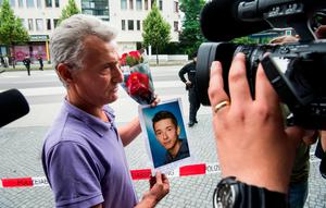 MUNICH, GERMANY - JULY 23: The father of one of the victims is showing flowers and a picture of his son (on the picture his son is named as Zabergja Dijamant) as he arrives outside the OEZ shopping center the day after a shooting spree left nine victims dead on July 23, 2016 in Munich, Germany. According to police an 18-year-old German man of Iranian descent shot nine people dead and wounded at least 16 before he shot himself in a nearby park. For hours during the spree and the following manhunt the city lay paralyzed as police ordered people to stay off the streets. Original reports of up to three attackers seem to have been unfounded. The shooter's motive is so far unclear. (Photo by Joerg Koch/Getty Images)