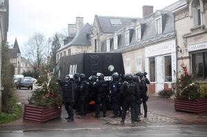French riot officers patrol in Longpont, north of Paris, France, Thursday, Jan. 8, 2015. Scattered gunfire and explosions shook France on Thursday as its frightened yet defiant citizens held a day of mourning for 12 people slain at a Paris newspaper. French police hunted down the two heavily armed brothers suspected in the massacre to make sure they don't strike again. (AP Photo/Thibault Camus)