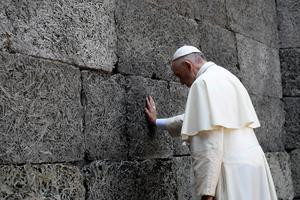 Pope Francis at Auschwitz, saying a prayer in front of the death wall