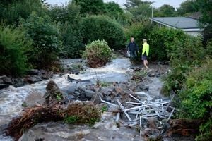 Rocks and debris cover a path after a brook burst its banks following flash flooding in the coastal village of Coverack in Cornwall.  Ben Birchall/PA Wire