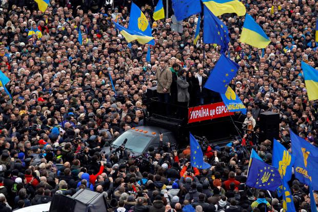 Lawmaker and chairman of the Ukrainian opposition party Udar (Punch), WBC heavyweight boxing champion Vitali Klitschko, left on the platform, waves a flag during a rally in downtown Kiev, Ukraine, on Sunday, Dec. 1, 2013. As many as 100,000 demonstrators chased away police to rally in the center of Ukraine's capital on Sunday, defying a government ban on protests on Independence Square, in the biggest show of anger over the president's refusal to sign an agreement with the European Union. (AP Photo/Sergei Grits)