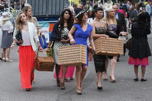 ASCOT, ENGLAND - JUNE 20:  Racegoers carry hampers to Ascot racecourse to attend Royal Ascot on June 20, 2013 in Ascot, England. The 'Royal Ascot' horse race meeting runs from June 18, 2013 until June 22, 2013 and has taken place since 1711. The racecourse is expected to welcome around 280,000 racegoers over the five days, including Her Majesty The Queen and other members of the Royal Family.  (Photo by Oli Scarff/Getty Images)