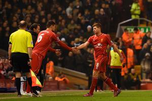 Liverpool's English midfielder Steven Gerrard (R) shakes hands with Liverpool's Croatian defender Dejan Lovren (L) as he is substituted during the English Premier League football match between Liverpool and Tottenham Hotspur at the Anfield stadium in Liverpool, northwest England, on February 10, 2015.