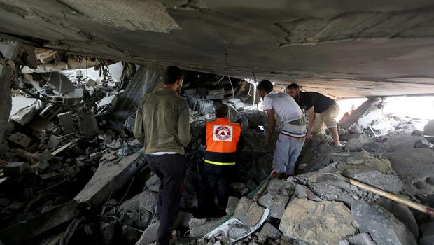 Palestinian medics search for possible victims under the rubble of a home destroyed by an Israeli strike in Khan Younis in the southern Gaza Strip, Friday, July 25, 2014.  (AP Photo/Hatem Moussa)