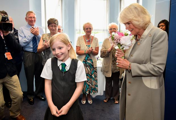 The Duchess of Cornwall receives flowers from Sophie Booker,ten, as she visits Ballyhackamore Credit Union in Belfast, Northern Ireland, as the Prince of Wales and Camilla, attend a series of engagements in Northern Ireland following their two day visit in the Republic of Ireland. PRESS ASSOCIATION Photo. Picture date: Thursday May 21, 2015. See PA story ROYAL Ireland. Photo credit should read: Jeff J Mitchell/PA Wire