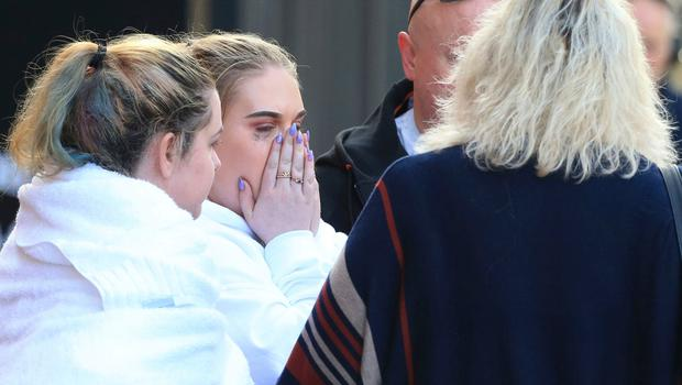 Fan leaves the Park Inn hotel in central Manchester, England, Tuesday, May 23, 2017. Over a dozen people were killed in an explosion following a Ariana Grande concert at the Manchester Arena late Monday evening. (AP Photo/Rui Vieira)