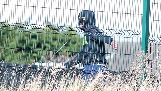 A masked youth throws stones at police in Lurgan. Presseye