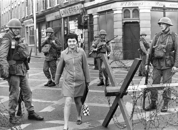 Riots : Belfast. August 1969.  Army take over:  a young lady leaves the sealed off area passing through the barricades in Divis Street.  16/8/69