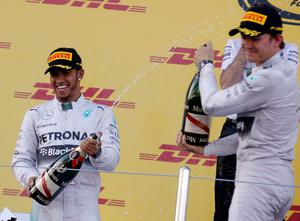 Winning Mercedes driver Lewis Hamilton of Britain, left, sprays champagne to his teammate second place Mercedes driver  Nico Rosberg of Germany on the podium of  the Formula One Russian Grand Prix at the 'Sochi Autodrom' Formula One circuit, in Sochi, Russia. (AP Photo/Luca Bruno)