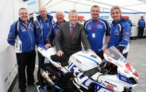 First Minister Peter Robinson pictured with Hector Neill and his team during his visit to the Tyco Suzuki base at the Vauxhall International 2014 North West 200 in Portrush.