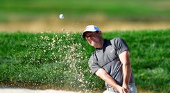 Warming up: Rory McIlroy plays from a bunker at Baltusrol