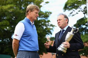 GULLANE, SCOTLAND - JULY 15:  Ernie Els of South Africa, the 2012 Open Champion returns the Claret Jug to Peter Dawson, Chief Executive of The R&A, ahead of the 142nd Open Championship at Muirfield on July 15, 2013 in Gullane, Scotland.  (Photo by Matthew Lewis/Getty Images)