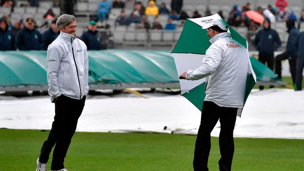 Blown away: Umpire Nigel Llong is amused as colleague Richard Illingworth bears brunt of the Dublin weather