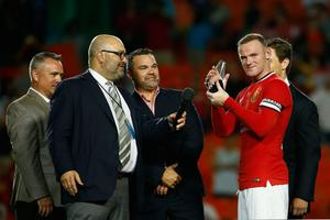 Wayne Rooney #10 of Manchester United holds the man of the match award following his team's victory over Liverpool in the Guinness International Champions Cup 2014 Final at Sun Life Stadium on August 4, 2014 in Miami Gardens, Florida. United defeated Liverpool 3-1.  (Photo by Chris Trotman/Getty Images)
