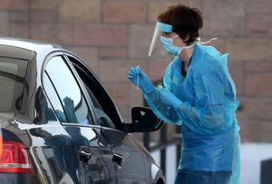 A nurse prepares to take a sample at a Covid-19 testing centre in the car park of the Bowhouse Community Centre in Grangemouth (Andrew Milligan/PA)
