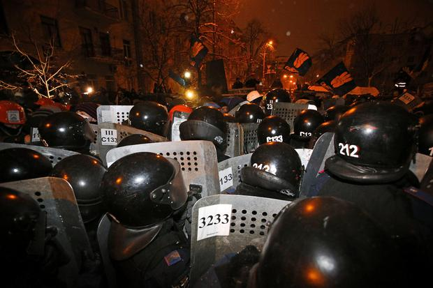 Riot police push pro-European Union activists away from their barricades at the Ukrainian presidential administration building in Kiev, Ukraine, Tuesday, Dec. 10, 2013.